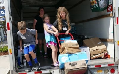 Children help load the truck that took supplies from the Packaged Good to Keller Williams' office in East Cobb, where Walton High football players helped make the transfer to a Super Movers semi.