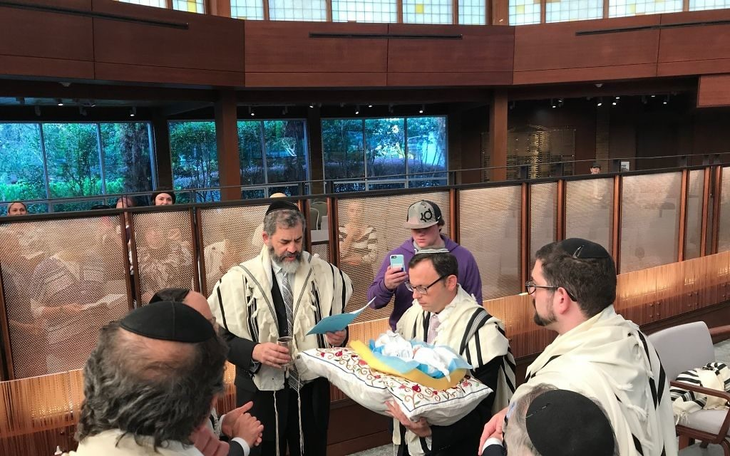 Rabbis Ilan Feldman and Adam Starr continue the Beth Jacob-Young Israel cooperation by officiating at the bris of the first evacuee baby born in Toco Hills.