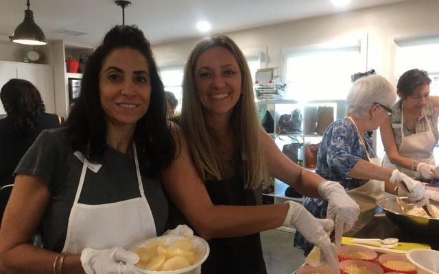 MICHELLE SIMON AND SAMANTHA KURGAN Michelle Simon (left) and the Packaged Good's Samantha Kurgan assemble cakes.