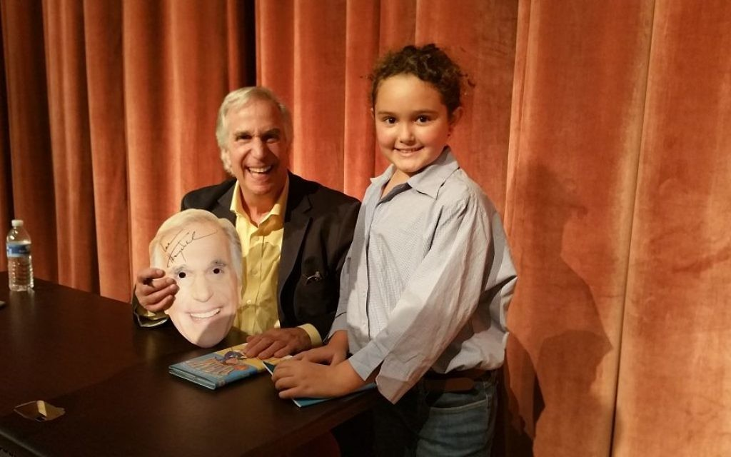 "Dylan Dickson — the 9-year-old author of ""Why Can't I Read?"" — meets her hero, fellow author and fellow person with dyslexia, Henry Winkler, at the Decatur Book Festival, where he was signing copies of one of his ""Hank"" series of books. Dylan, who wore a Winkler mask to the event, will join Gail Saltz at her appearance at the Book Festival of the Marcus JCC on Nov. 5."