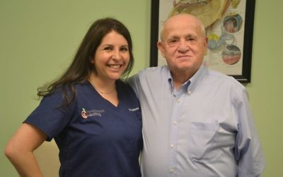 Peachtree Hearing audiologist Melissa Wikoff and Holocaust survivor Hershel Greenblat are all smiles after Greenblat gets his hearing aids.
