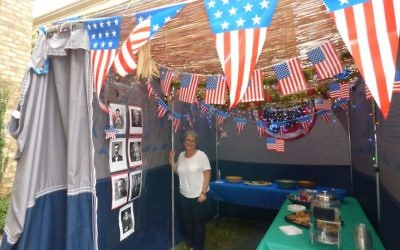 "Rabbi Judith Beiner stands in her and husband Stan's sukkah, which highlights the theme of ""United States of Sukkah."""