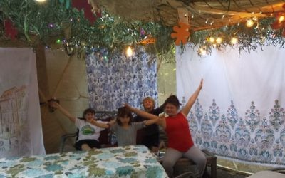 The children of Rabbi Laurence and Brooke Rosenthal enjoy their sukkah's eclectic style.