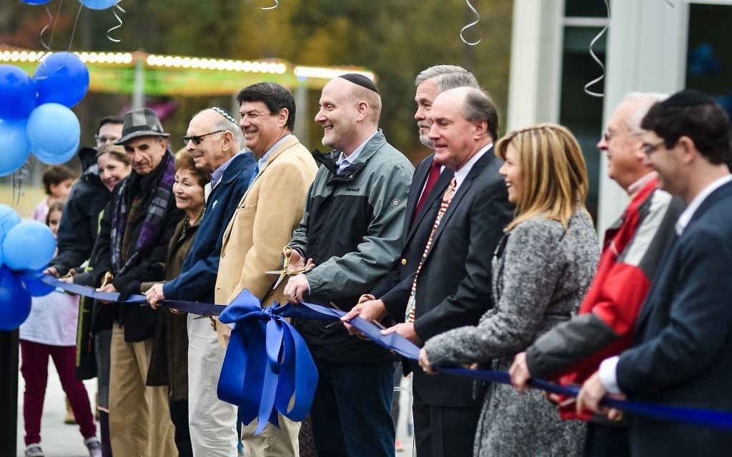 Photo courtesy of Beth Intro Photography Surrounded by supporters including Sandy Springs Mayor Rusty Paul, AJA Head of School Rabbi Ari Leubitz cuts the blue ribbon in front of the new Upper School building.