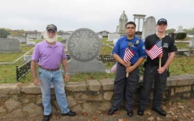 Explorers and Fred Ross help plant flags at Greenwood Cemetery.