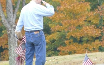 Barry Benator salutes after planting a new flag at the grave of a Jewish military veteran.