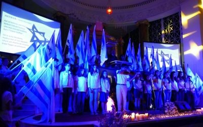 "Israel Scouts hold Israeli flags during the singing of ""Hatikva"" at the conclusion of the community Yom HaZikaron ceremony April 30, 2017, at The Temple."