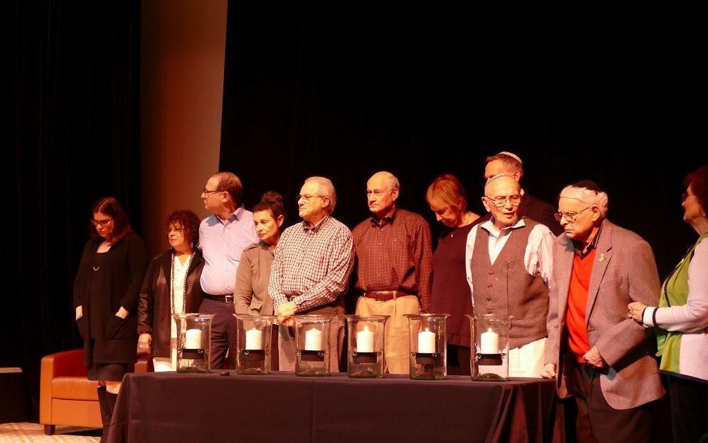 (From left) Alexandra Zapruder, Peggy Klug, Isaac Klug, Gina Karp, Harry Scheinfeld, Morray Scheinfeld, Susan Scheinfeld, Ken Winkler, Bernie Gross, Abe Besser and Marlene Besser recite the Mourner's Kaddish.