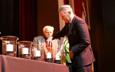 Abe Besser watches as JCC Vice Chairman Ken Winkler lights a candle.