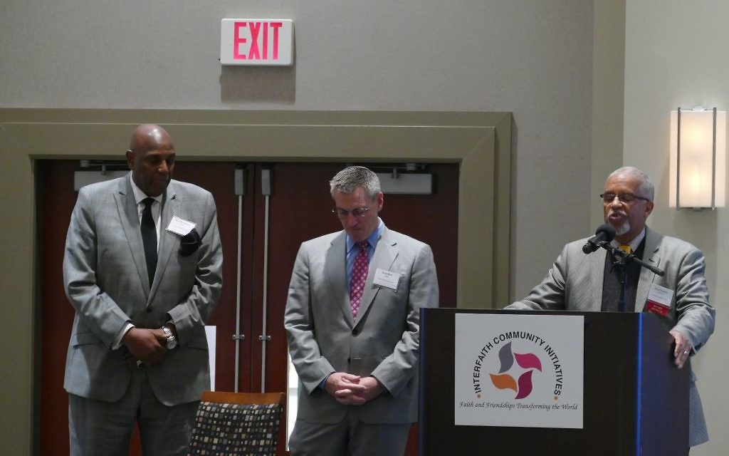 Temple Sinai Senior Rabbi Ron Segal joins the Rev. Gerald Durley (left) and Imam Plemon El-Amin (right) for closing prayers at the Interfaith Community Initiatives luncheon Nov. 15, 2017.