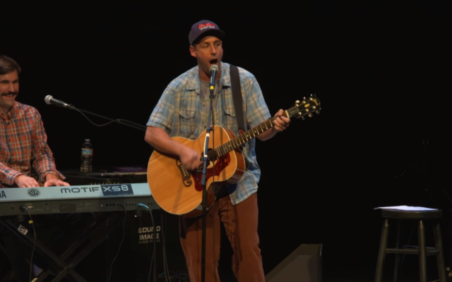 """Adam Sandler delivers the fourth version of his iconic """"Chanukah Song"""" in San Diego in 2015. (YouTube screen grab)"""