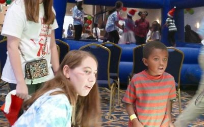A game of Skee-Ball proves fun for a young participant and teen volunteers.