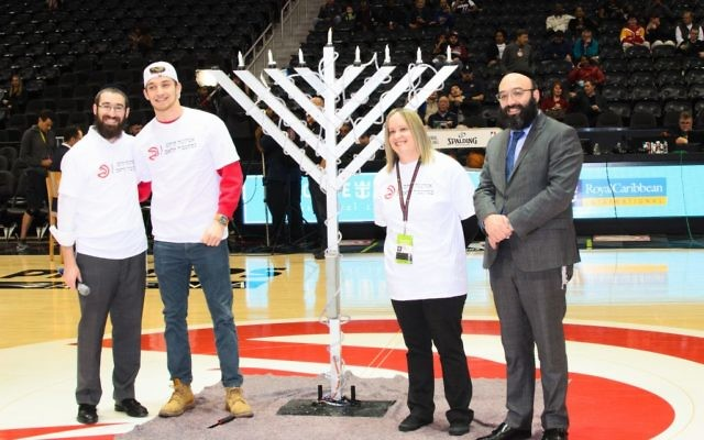 Rabbi Yale New, Ben Massey, Emily Hanover and Rabbi Isser New bask in the light of the menorah before tipoff of the Hawks' home game against the Heat.