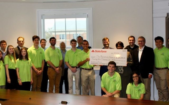 Surrounded by his team, local State Farm agents and Dean Benjamin Ayers from the Terry College of Business, Backpack Project founder Zack Leitz is presented a $25,000 check from the State Farm Neighborhood Assist program in Correll Hall at the University of Georgia on Dec. 6.