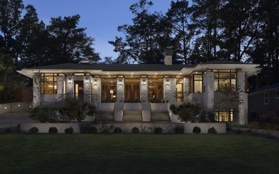 The house glows at night, showcasing three sets of steps in line with French doors in the Frank Lloyd Wright-style design.
