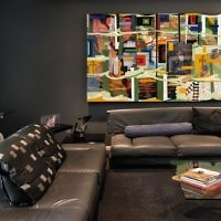 """The living room features Judy McKee's sculpted table (left), Kari Russell-Pool's glass sculpture """"Tea Pot Trophy,"""" Carlo Maria Mariani's oil painting """"In Spite of It All"""" and Radcliffe Bailey's mixed-media work """"Flikaflame."""""""