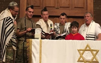Retired Navy Capt. Neil Block (right) and 11-year-old Avi Heart join U.S. Army troops on the bimah of the Regimental Chapel at Fort Benning on Dec. 3. (Photo by Ahava Heart)