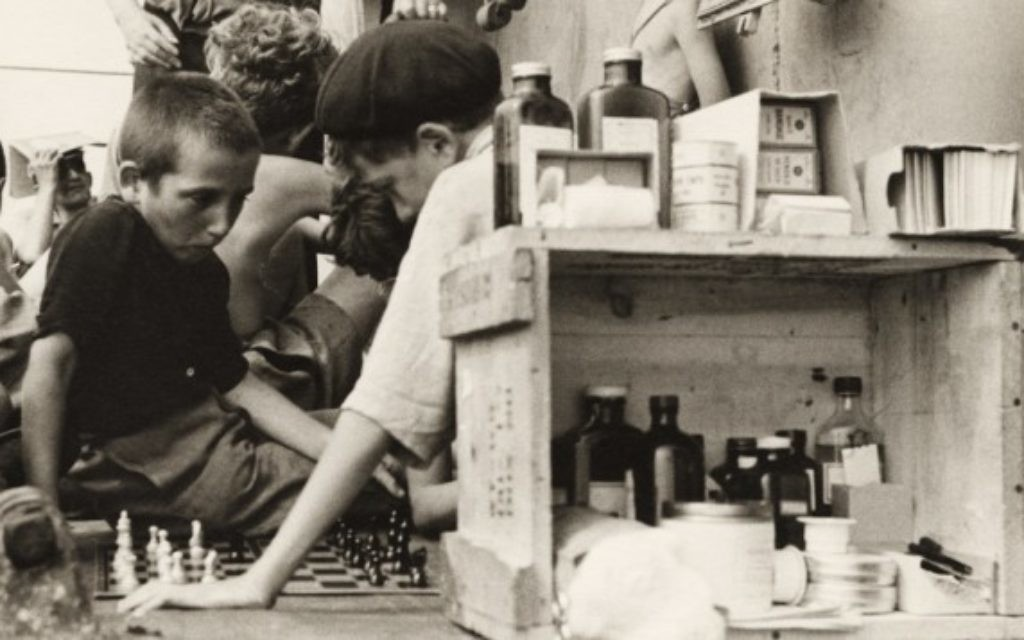 Children playing chess on the refugees' deck of the Henry Gibbins next to an outdoor medical station and pharmacy, 1944. (photo credit: Ruth Gruber)