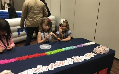 Addison Gehram (left) and Lexie Halpern make looms at the booth representing In the City Camp, a Jewish day camp entering its sixth summer.