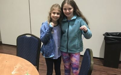 Maya Israel (left) and Abigail Richman, both 10, show off lanyards they made with Camp Judaea counselors.