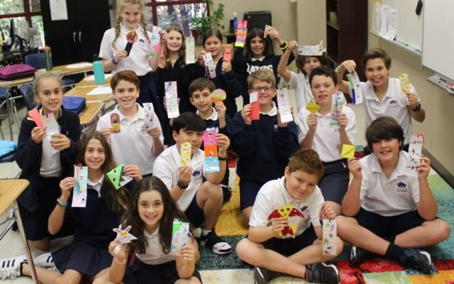 Davis Academy sixth-graders show the bookmarks they received from Russia.