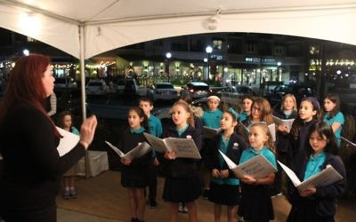 "The Davis Academy Magical Melodies sing ""Mi Yimaleil"" at Town Brookhaven before a menorah lighting with The Temple."