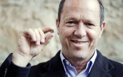 """Jerusalem Mayor Nir Barkat, holding the clay artifact, says, """"It is very overwhelming to receive greetings from First Temple-period Jerusalem. This shows that already 2,700 years ago, Jerusalem, the capital of Israel, was a strong and central city."""" (Photo by Yoli Schwartz, Israel Antiquities Authority)"""