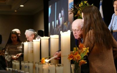 Survivors Ben Hirsch (left) and Hershel Greenblat light candles during the Am Yisrael Chai commemoration.