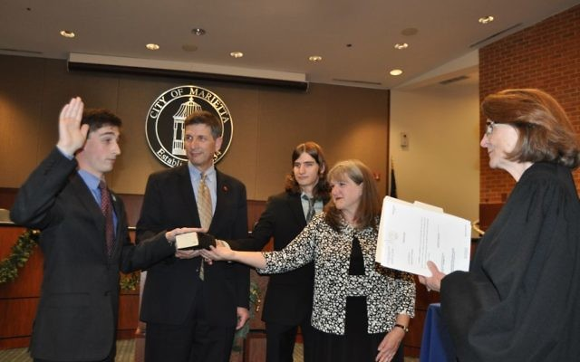 Joseph Goldstein takes the Marietta City Council oath of office Dec. 18, administered by Senior Superior Court Judge Adele Grubbs. Holding the Tanakh are his father, outgoing council member Philip Goldstein; his brother, David Goldstein; and his mother, Elise Goldstein.