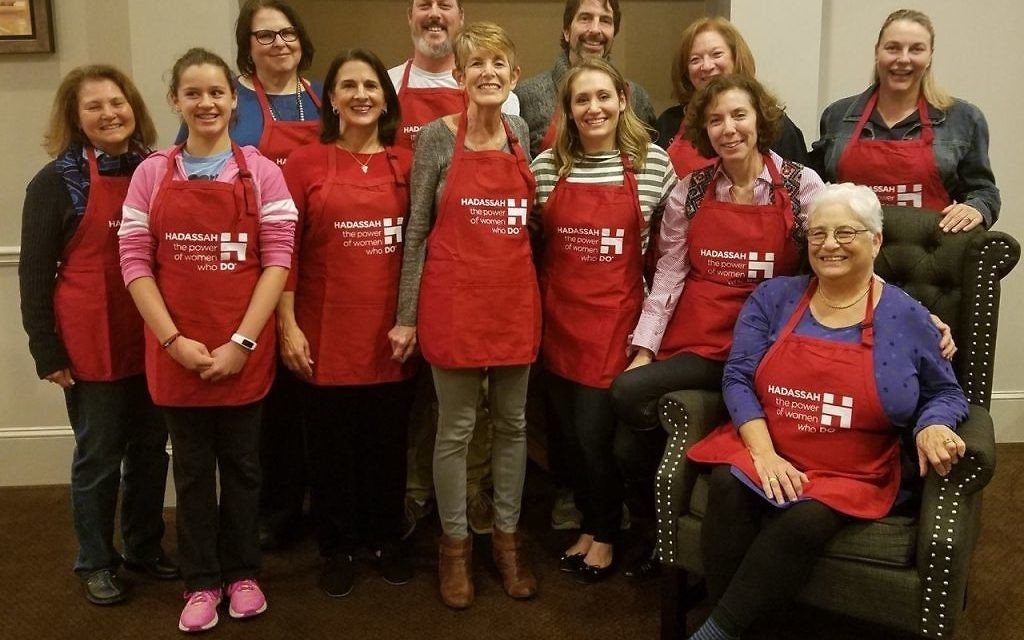 """Almost Chopped"" participants gather at Spring Hall for a run-through on Dec. 19: (from left) Hadassah Greater Atlanta President Sheila Dalmat; Kinneret Weismark, runner, Kathy Sheehan, chef-testant, and Pam Leinmiller, sous chef, Team Sugar and Spice; Andy Stenmark, sous chef, Team Hash Slingers; Barbara Lang, event co-chair; Glen Caruso, chef-testant, Team Hash Slingers; Samantha Ellis, chef-testant, Team Samantha Lives Next Door; Holly Strelzik, event co-chair; Judi Schnitzer, sous chef, Team Jersey Tomatoes; Michelle Venter, MC; and (seated) Barbara Flexner, chef-testant, Team Jersey Tomatoes. Not shown are Michele Vernon, Rebecca Carey, Eliana Leader and Tristan Bjorn Stenmark."