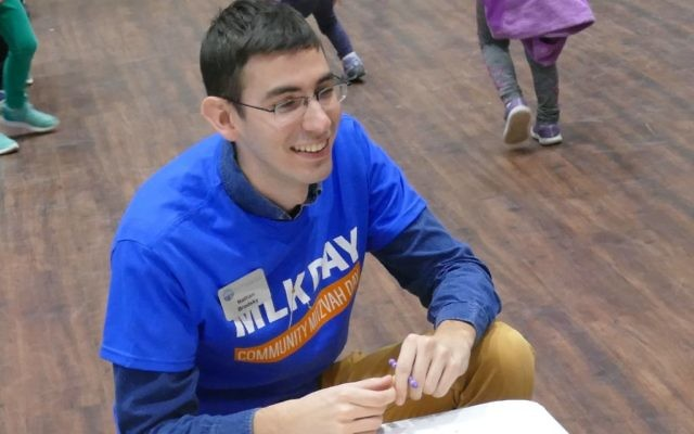 PJ Library's Nathan Brodsky provides guidance at one of the card-making tables.