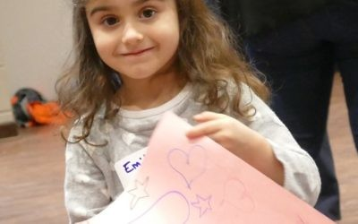One young volunteer shows off the card she created.