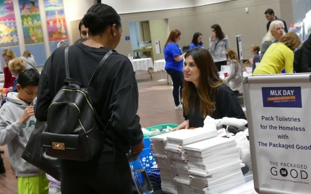 Joanna Estroff from The Packaged Good welcomes volunteers interested in packing care bags of toiletries.