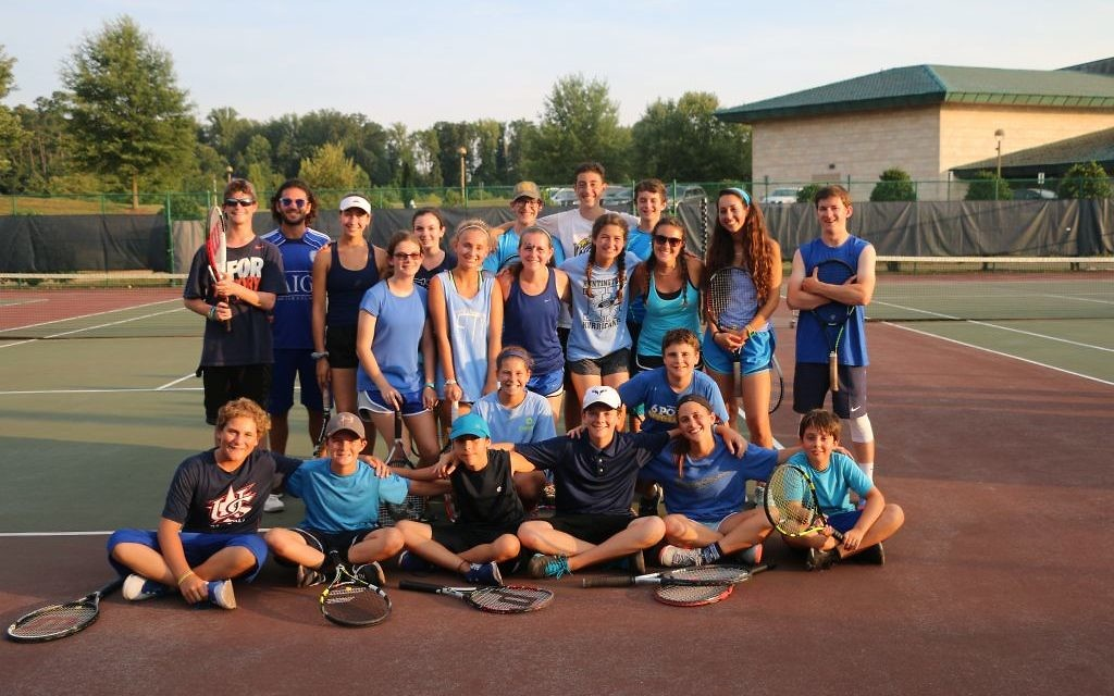 Upper-level tennis players at one of the two 6 Points Sports Academies get together before warming up for an event under the lights.