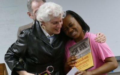 "Photo by Michael Jacobs RuthE Levy, the owner of bookstore And Thou Shalt Read, presents Enlighten America essay contest winner Icesha Sanders with one civil rights book for her and one for Marietta Middle School as part of a prize package that also included awards from B'nai B'rith and from the Marietta/Cobb County Communities in Schools program. Art Link is behind them. The essay contest ""is a program that I support with my heart and with my soul,"" Levy said."