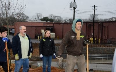 Greg Levine (right), the co-executive director and chief program officer of Trees Atlanta, sets an example for the volunteers.