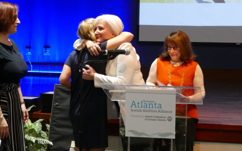 Photo by Sarah Moosazadeh Gena Boyle looks on as Jaime Russo and Sheryl Arno embrace after Ina Enoch praises Arno for her work to promote inclusivity in the community.