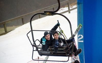 Yehuda Deutsch (left) and Tzvi Cavalier head up the ski lift for another run. (Photo by Eli Gray)