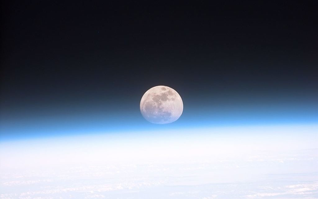 The full moon is seen through the haze of Earth's atmosphere from the space shuttle Discovery on Dec. 21, 1999.