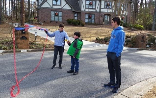 Micah Bronfman (left) helps Sammy Lesser with a kite while Yaniv Zigmond stands by during a recent Sunday playdate in the Friends@Home program.