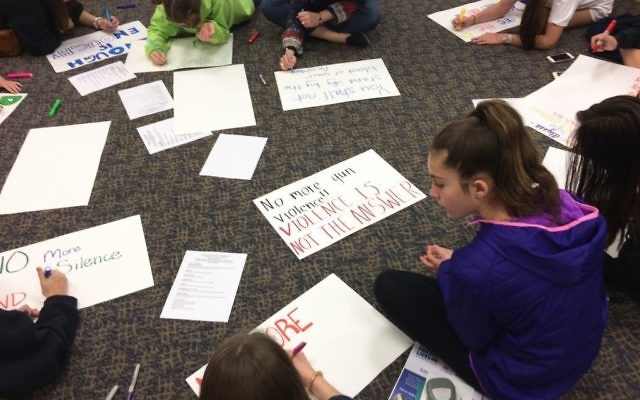 Middle-schoolers at Temple Emanu-El work on posters March 18 for the March for Our Lives on March 24. (Photo by Bob Bahr)
