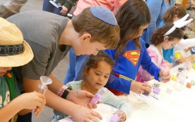 The rain forced some activities inside, but children doing sand art don't seem to mind.