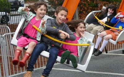 Pearl, Menny and Henia Schusterman enjoy one of the outdoor carnival rides.