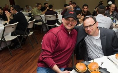 Emcee Justin Katz (left) and Rabbi Adam Starr prepare to eat the second course, consisting of Jack Daniel's burgers and Cajun kettle chips.