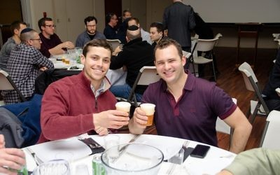 Tommy Neustein (left) and AJT 40 Under 40 member Eli Wolfe toast with Goose IPA from Goose Island Beer.