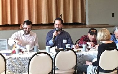 JF&CS CEO Rick Aranson enumerates the Ten Plagues as Rabbi Ari Kaiman and Josiah Benator dip.