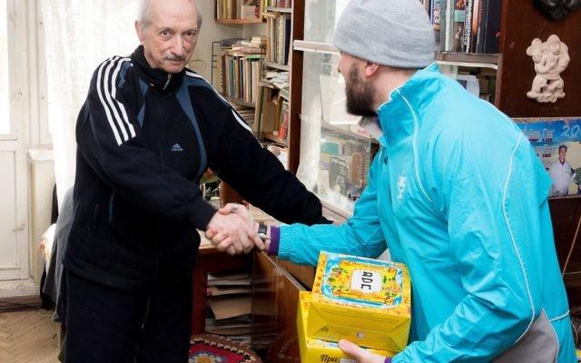 Photo courtesy JDC A JDC Jewish community youth volunteer delivers matzah to a needy Jewish senior before Passover in Kishinev, Moldova.