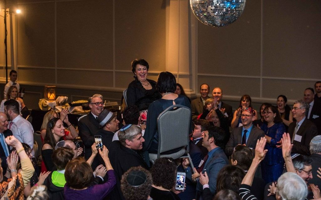 Honorees Susan Sandler (left) and Brooke Rosenthal get a lift during the hora. (Photo by Montoya Turner, Made You Look Photo & Film)
