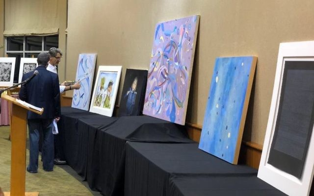 Anthony Naturman is among the guests perusing Hendel Futerfas' artwork at the Chaya Mushka Children's House fundraiser April 22 at Congregation Beth Tefillah.