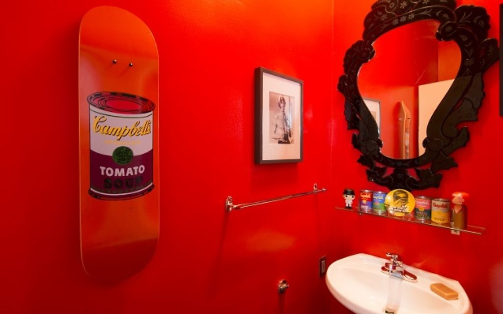 "The powder room pays homage to Andy Warhol. The shocking paint color is Benjamin Moore's Simply Red. The autograph on the David Bowie photograph is addressed to Buxbaum — ""Thanks for the use of your gaffe (and the sounds)"" — after Bowie spent the day at his apartment. The mirror is a Venetian replica. (Photo by Duane Stork)"